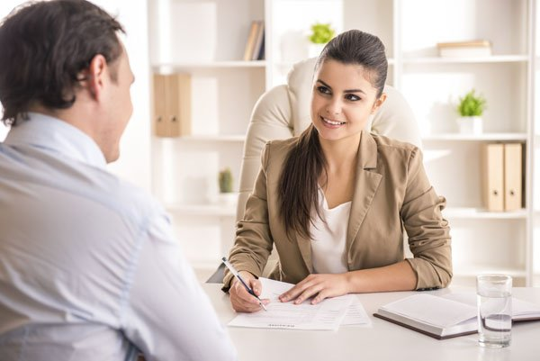 Businesswoman interviewing male candidate for job in office or leading and managing her team
