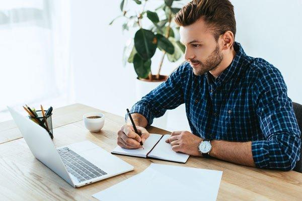 Man-studying-online-taking-notes-ecourse-webinar-Depositphotos_219003202
