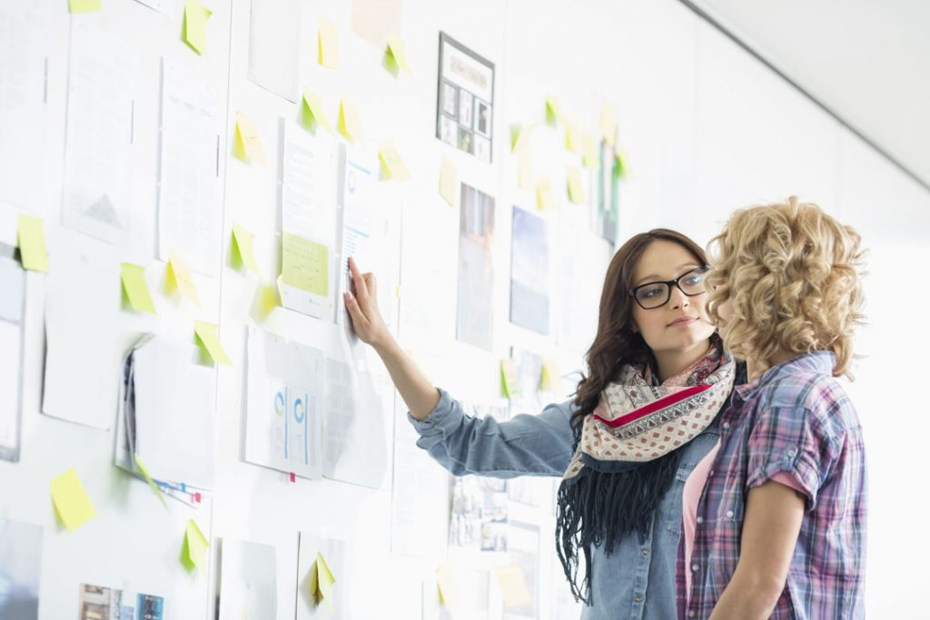 Creative businesswomen discussing business plans over papers stuck on wall in office