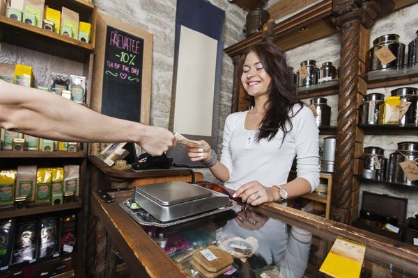 Smiling young salesperson selling accepting money from customer in tea store